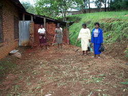 women leveling the plot for the construction of the farm house