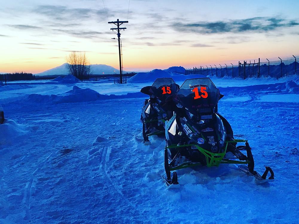 Iron Dog Team 15's sleds against the sunset in McGrath Alaska.
