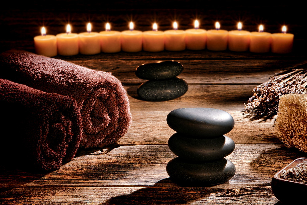 Spa setting with towels, candles and hot stones.