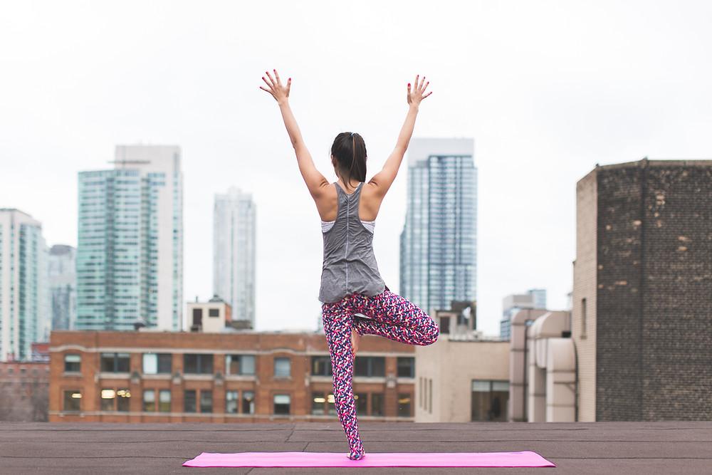 Femme qui fait du yoga sur  un toit en ville