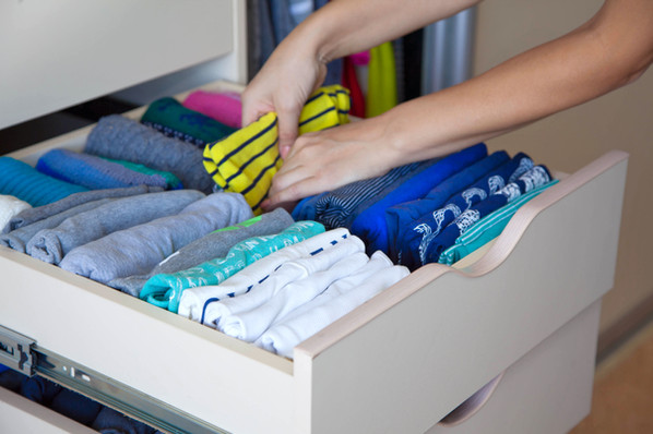 The woman folds t-shirts in the drawer.