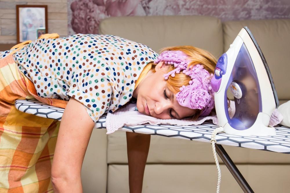 vrouw slapend bij strijkplank