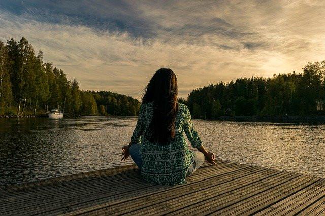 vrouw yoga aan de waterkant