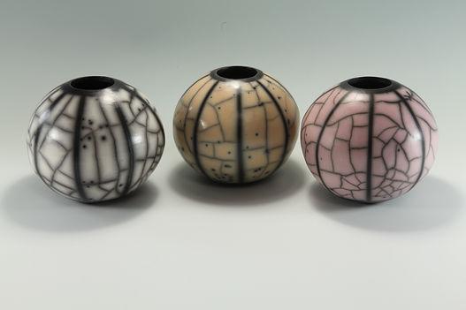 Three naked raku spheres in various colours