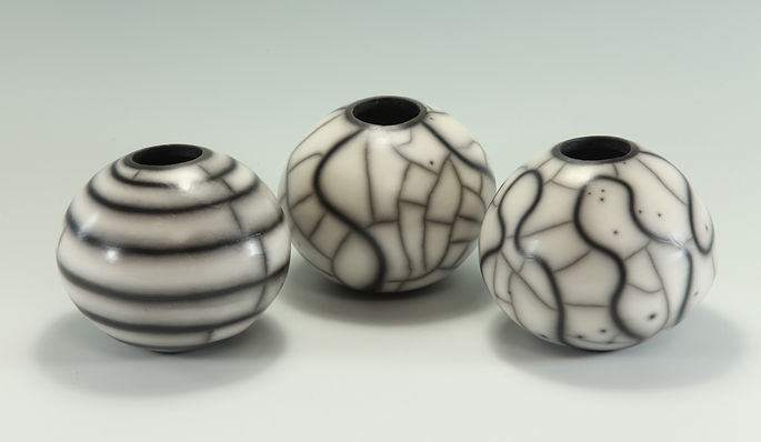 Three small pots with a variety of surface decoration