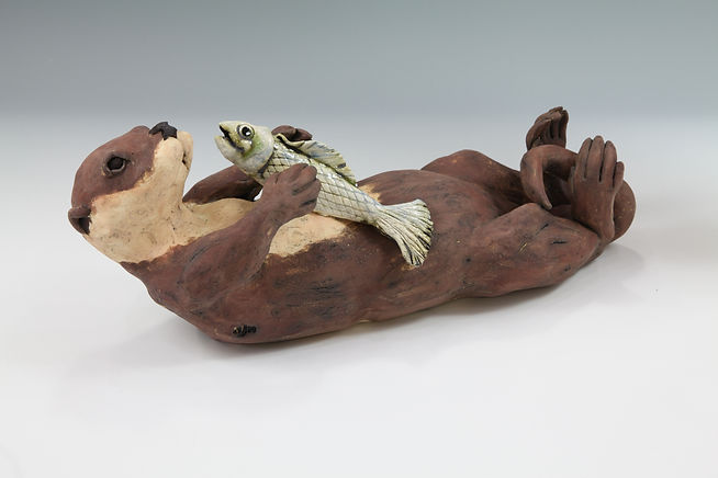 Otter with fish - decorated with coloured slips and oxides.