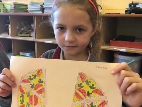 First Class have been learning about fractions. We folded shapes in half and we made paper pizzas.
