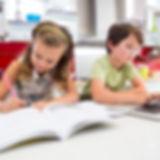 girl-doing-her-homework-while-boy-using-