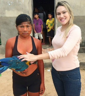 Repórter Fabíola Gomes se encanta com a arara da aldeia. (Foto: Reprodução/É Bem MT)