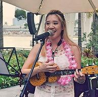 Girl playing baritone ukulele singing