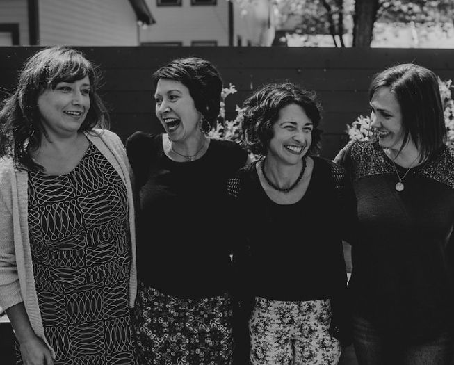 four smiling midwives standing together