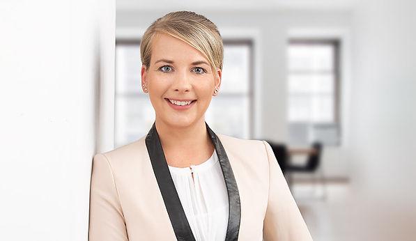 Modernes Bewerbungsfoto einer Frau mit hellem Blazer, die in einem hellen Büro an der Wand gelehnt steht