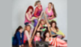 JGA Fotoshooting von Junggesellinen im lustigem 90er Jahre Disko Outfit posen auf einer Holzleiter