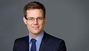 Klassisches Bewerbungsfoto eines seriösen Mannes mit blauer Krawatte vor dunkelgrauem Hintergrund
