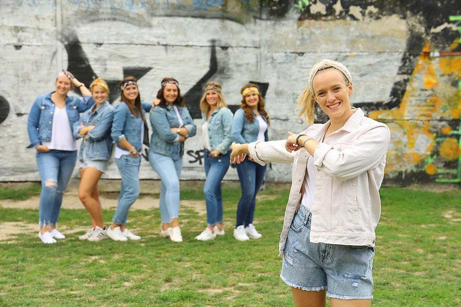 Bei einem JGA Fotoshooting von Junggesellinnen zeigt die Braut im Vordergrund auf ihre lächelnden Freundinnen im Jeans-Outfit