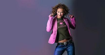 Portraitfot einer tanzenden jungen Frau mit rosa Jacke.