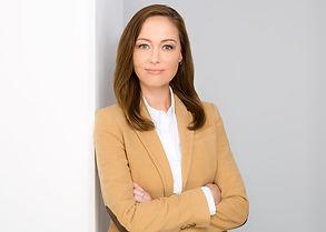 Modernes Bewerbungsfoto einer Frau mit verschränkten Armen und beigen Blazer vor weißem Hintergrund.