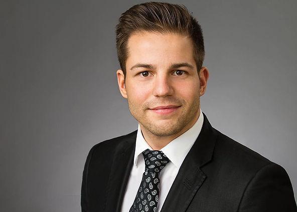 Modernes Bewerbungsfoto eines Mannes mit Anzug und Krawatte mit Paisleymuster vor grauem Hintergrund