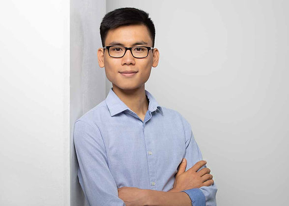 Modernes Bewerbungsfoto eines asiatischen jungen Mannes, mit Brille und blauem Hemd. der locker an einer Säule lehnt vor einem hellen Hintergrund.