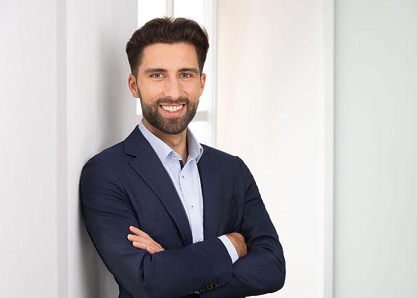Modernes Bewerbungsfoto eines offen lächelnden Mannes mit Vollbart und blauem Hemd vor einem hellen Bürohintergrund.