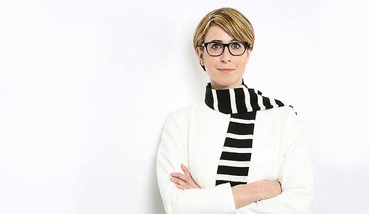 Modernes Bewerbungsfoto einer Frau mit verschränkten Armen und kurzen, blonden Haaren vor weißem Hintergrund.
