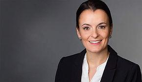 Modernes Bewerbungsfoto einer Frau mit kurzen, dunklen Haaren vor dunklem Hintergrund.
