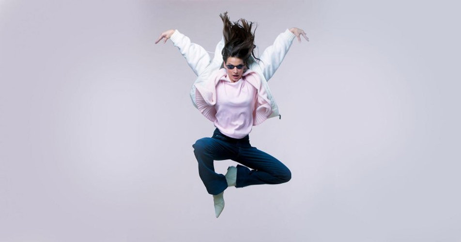 Portraitfoto einer Fau mit Sonnenbrille die im Stil von Matrix springt.
