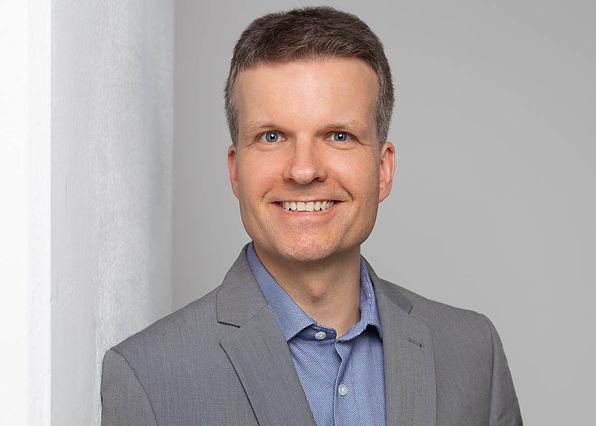 Modernes Bewerbungsfoto eines Mannes, der in einem grauen Sakko und blauem Hemd vor einem hellen Hintergrund an einer Säule lehnt