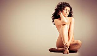 Aktfoto einer auf dem Boden sitzenden Frau mit lockigen Haaren
