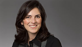 Modernes Bewerbungsfoto einer Frau mit schwarzen Haaren vor dunkelgrauem Hintergrund.