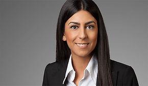 Modernes Bewerbungsfoto einer Frau und langen, schwarzen Haaren vor grauem Hintergrund