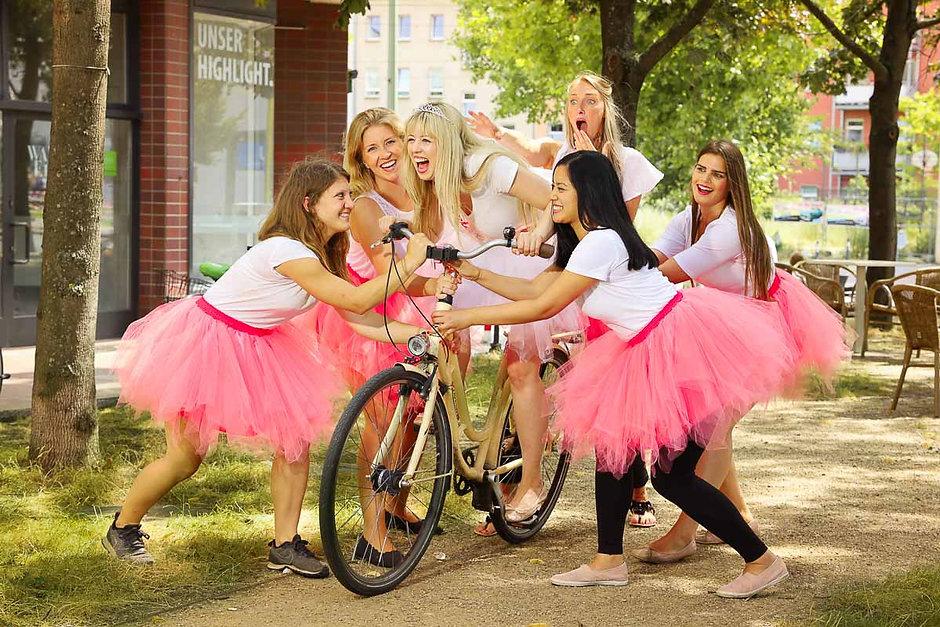 JGA Fotoshooting von Junggesellinnen im rosa Tütü die eine auf dem Fahrrad flüchtende Braut festhalten wollen