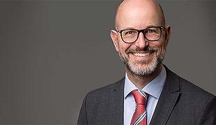 Modernes Bewerbungsfoto eines freundlich lächelnden Mannes mit Brille, Vollbart und roter Krawatte vor grauem Hintergrund.