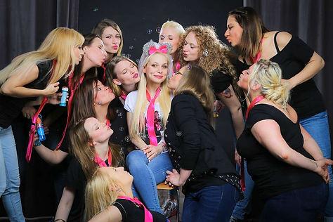 Junggesellinnen mit rosa Krawatten bilden einen Kreis um die Braut beim JGA-Fotoshooting um sie zu küssen.