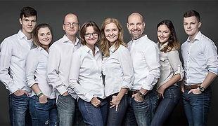 Familienfoto in Jeans und weißen Hemden von zwei Familien. Die Eltern mit Ihren erwachsenen Töchtern und  Söhnen.
