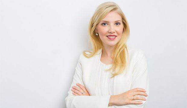 Modernes Bewerbungsfoto einer Frau mit verschränkten Armen und langen, blondenn Haaren vor weißem Hintergrund.
