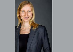 Modernes Bewerbungsfoto einer Frau und langen, blonden Haaren dunkelgrauen Hintergrund