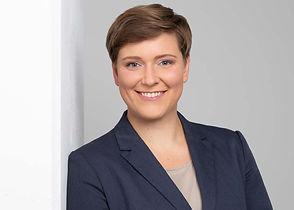 Modernes Bewerbungsfoto einer Frau mit kurzen, braunen Haare und einem blauen Blazer vor einem hellen Hintergrund.