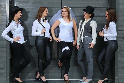 Die als Männer mit Bärten verkleideten Freundinnen schauen bei einem JGA Fotoshooting von Junggesellinnen auf die herausvordernd blickende Braut