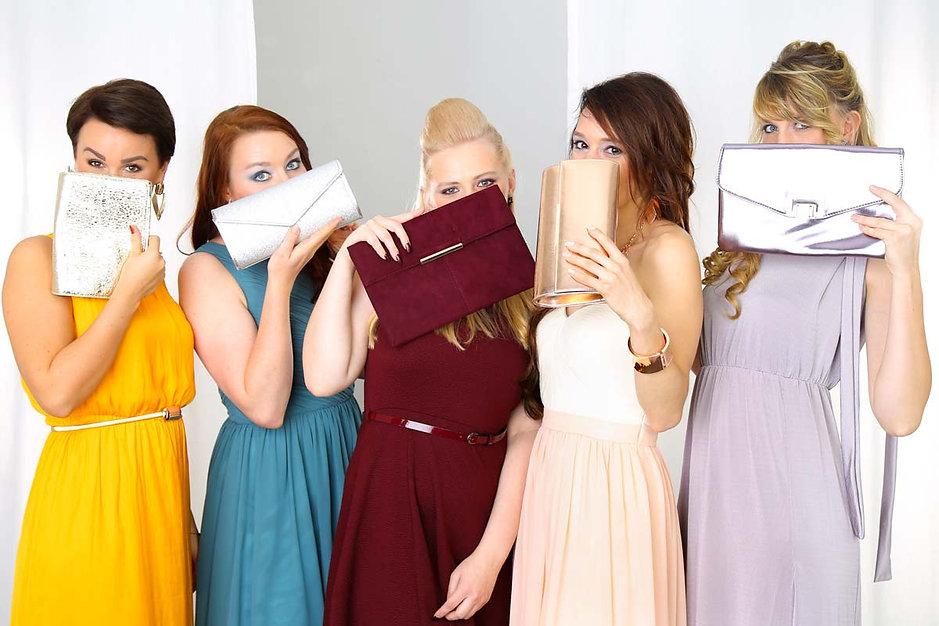 Fünf junge Frauen verstecken sich beim JGA-Fotoshooting bei Ihrem Junggesellinenabschied im Fotostudio Farbtonwerk in Berlin hinter Ihren zu Ihren farbigen Kleidern passenden Handtaschen.