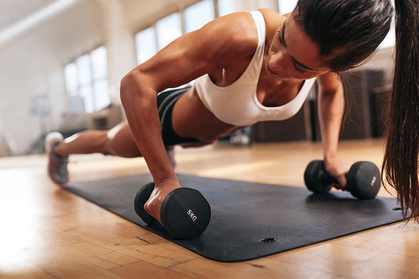 gym-woman-doing-pushups-on-dumbbells-PVC