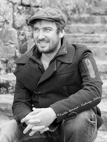 Quentin Ostanel souriant assis près d'un mur de pierre, cours d'impro