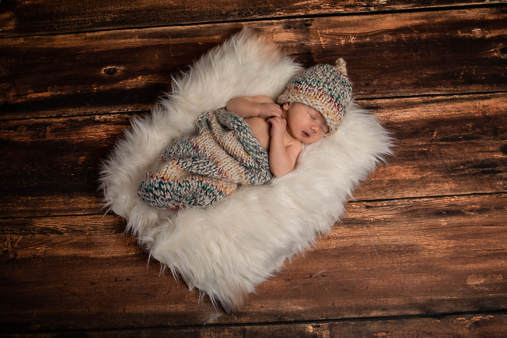 newborn cocoon, knit hat, newborn session, baby on a faux fur