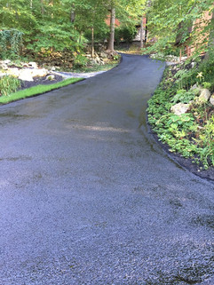 Just paved winding driveway through wood