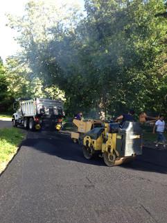 Paving crew using steamroller