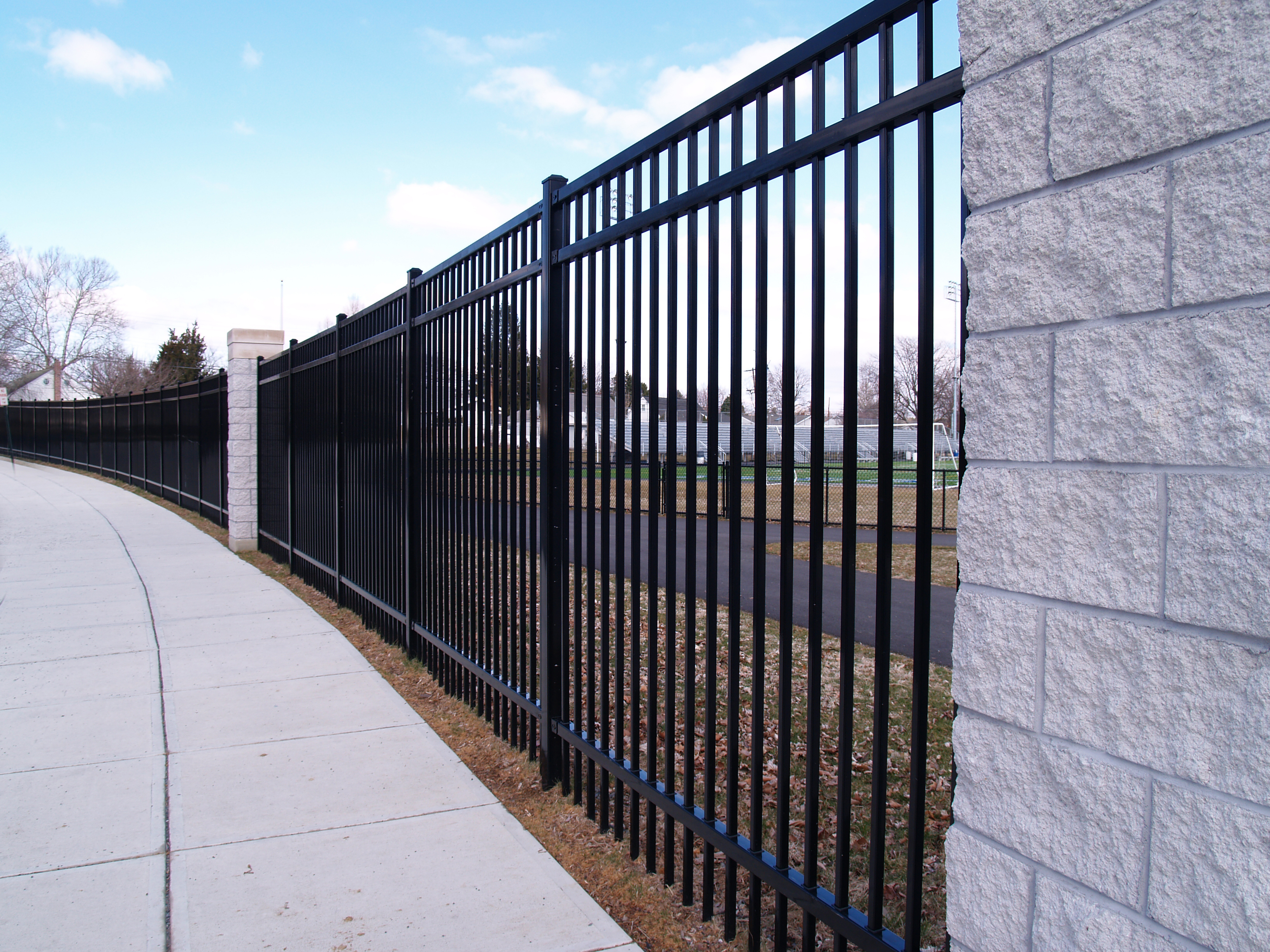 Tall Curving Black Fence By A Sidewalk.jpg
