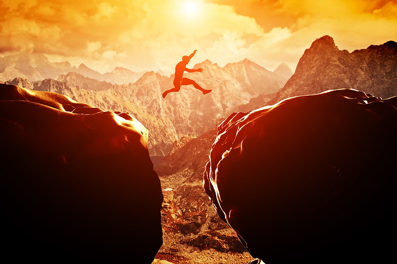 Man jumping over precipice between two r