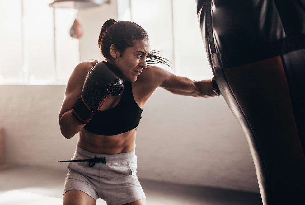 Female boxer hitting a huge punching bag