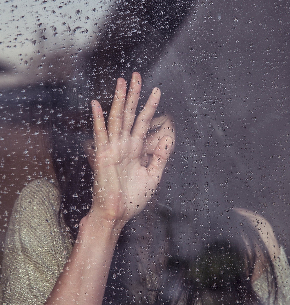 Sad woman at a window with rain outside
