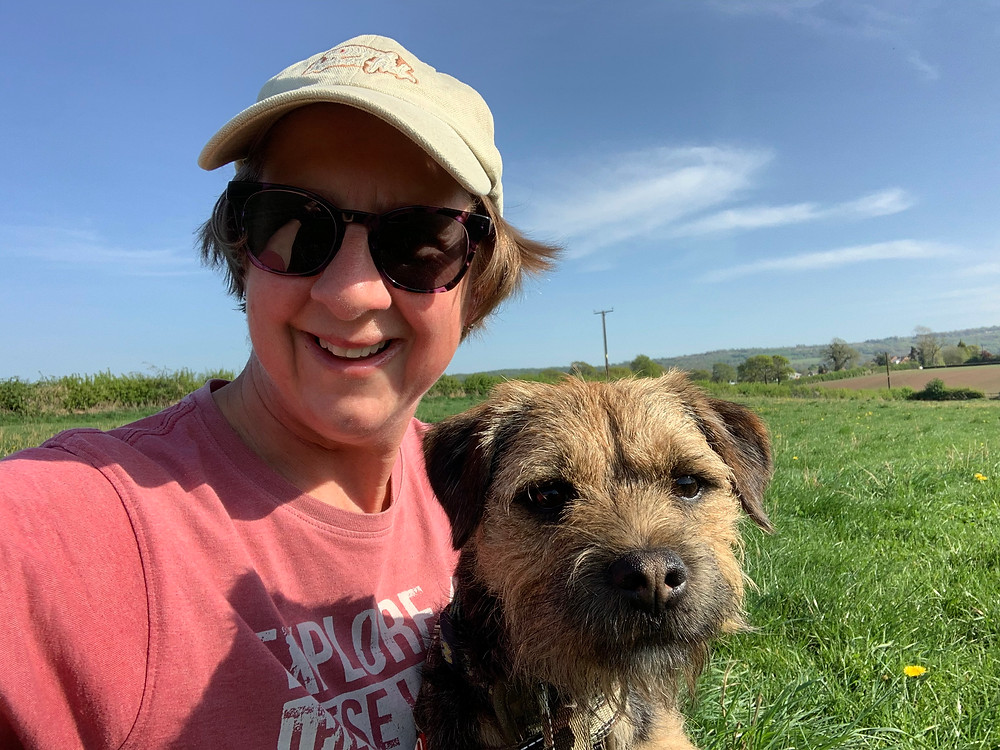 Woman and border terrier in the countryside